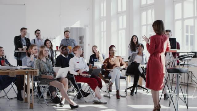 vídeos de stock, filmes e b-roll de red epic os empresários multiétnicos felizes levantam as mãos, ouvem o treinador do sexo feminino no seminário de escritório moderno em câmera lenta. - nova empresa