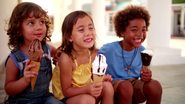 Happy multi-ethnic children eating ice-cream on summer holidays Smiling multi-ethnic children eating ice-cream and having fun together on family summer vacations ice cream stock videos & royalty-free footage