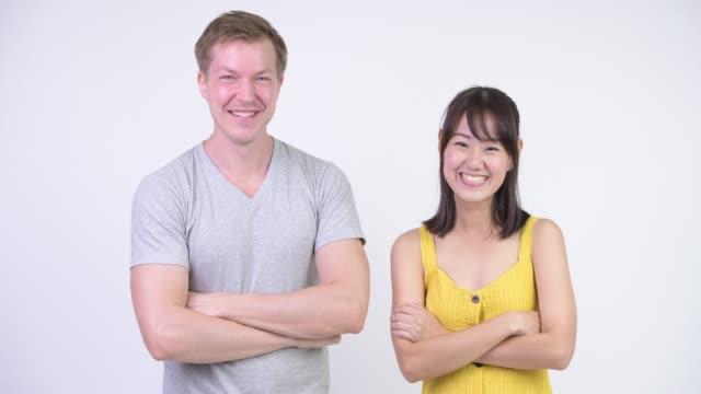 Casal multi-étnico feliz recebendo boas notícias com os braços cruzados - vídeo
