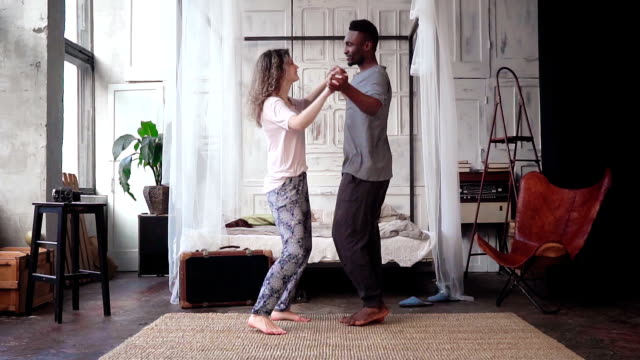 Happy multiethnic couple in pajamas dancing together. Man and woman hugs, falls on the bed and kisses. Slow motion video