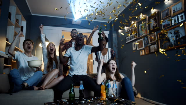 Happy multiethnic friends fans get crazy watching sports game at home, shout, celebrate win with confetti slow motion. video
