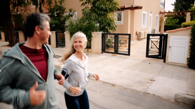 Happy multi-ethnic mature couple jogging together on suburban streets Active multi-ethnic senior husband and wife exercising together and running outdoors in spring healthy lifestyle stock videos & royalty-free footage