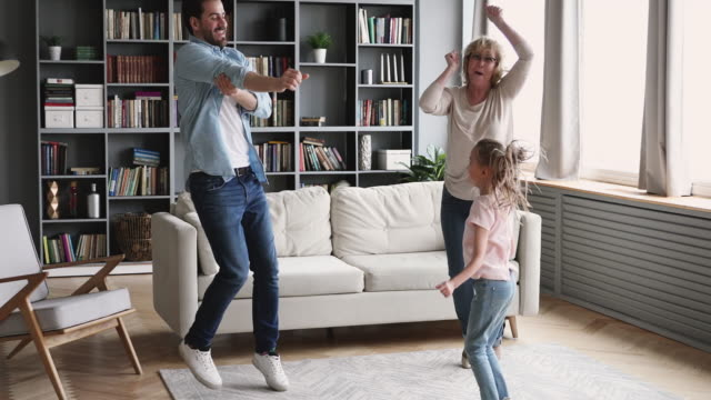 Happy multigenerational family having fun dance together in living room