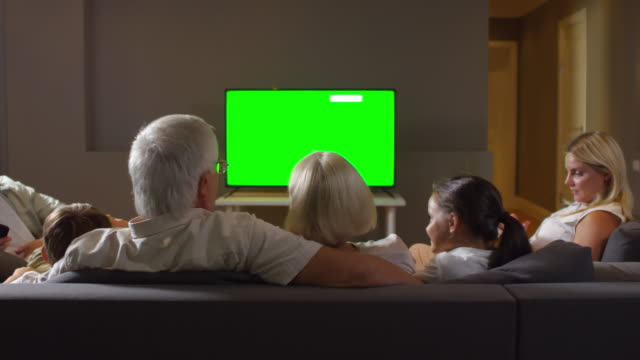 Happy Multigenerational Family Watching TV on Sofa and Chatting Happy mother, father, grandparents and kids sitting together on sofa in the living room, smiling and chatting while watching TV with chroma key screen family watching tv stock videos & royalty-free footage
