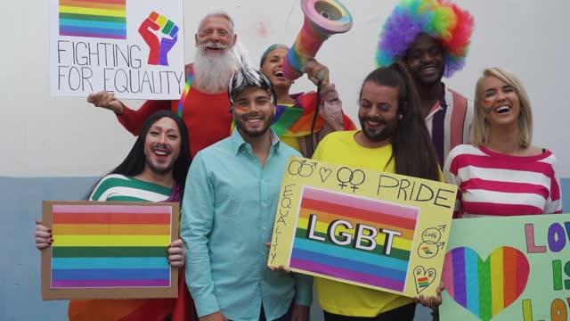 vídeos de stock, filmes e b-roll de feliz multiracial celebrando evento de orgulho gay - grupo de amigos com diferentes idades e raça lutando pela igualdade de gênero - conceito de protesto lgbt - lgbt