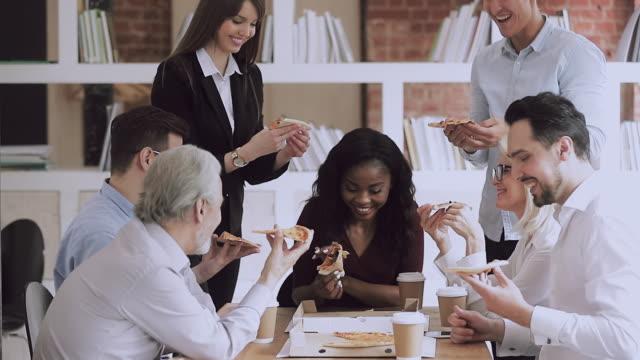 stockvideo's en b-roll-footage met gelukkige multiraciale jonge en oude zakenlui delen pizza in office - lunch