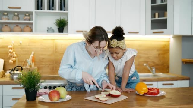 glückliche multiracial junge familie in der küche zu hause. internationale mutter und tochter kochen mittagessen. mama schneidet einen apfel für ihr kleines afrikanisches mädchen. kinderuhren verarbeiten leidenschaftlich und sorgfältig - afro amerikanischer herkunft stock-videos und b-roll-filmmaterial