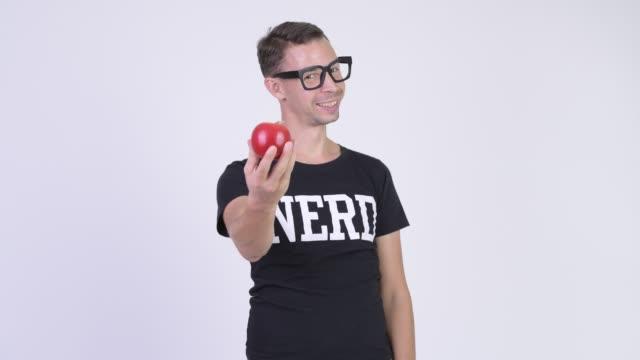 Homem feliz do lerdo com os eyeglasses que dão a maçã vermelha - vídeo
