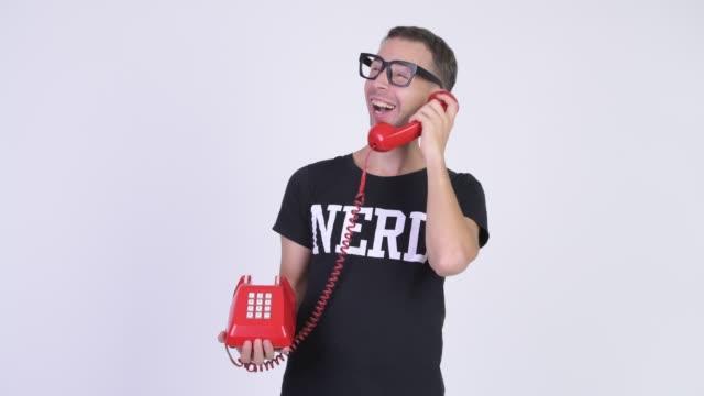 Homem feliz do lerdo com os eyeglasses que falam no telefone velho - vídeo