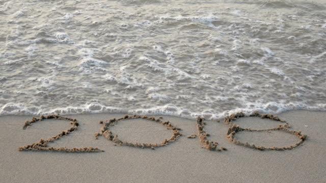 vidéos et rushes de 4k bonne année 2019. écriture de nombre 2018 sur une plage sablonneuse, vague splash changement à 2019 avec le son des vagues de l'océan. compte à rebours pour bonne année tournant issus de séquences vidéo de l'année 2018 à 2019 - 2018