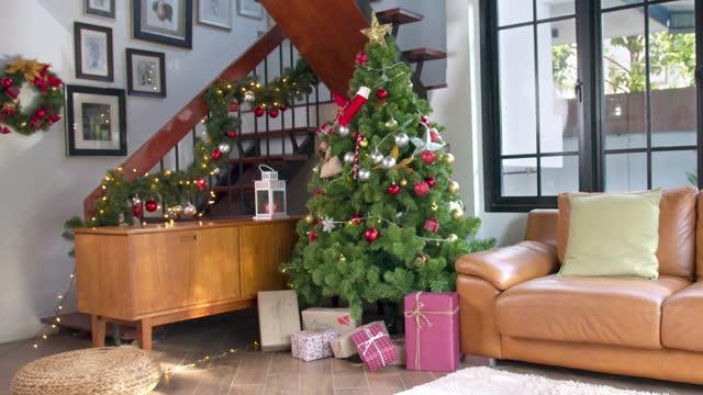 mutlu yeni yıl ve mutlu noeller, oturma odasında süslenmiş noel ağacı, yeni yıl kavramı ve noel arka plan kavramı - süslü püslü stok videoları ve detay görüntü çekimi