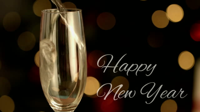 vidéos et rushes de bonne année écrite devant le champagne étant versé et lumières - flûte à champagne