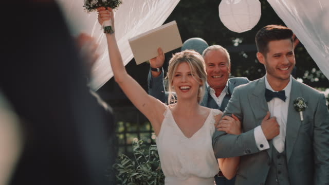 Happy newlywed couple greeting guests in ceremony Cheerful mature minister cheering for newlyweds. Happy young bride and bridegroom walking arm in arm while greeting guests. They are enjoying during wedding ceremony. newlywed stock videos & royalty-free footage