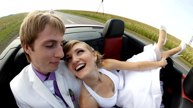Happy newlyweds in a car Happy newlyweds in convertible car newlywed stock videos & royalty-free footage