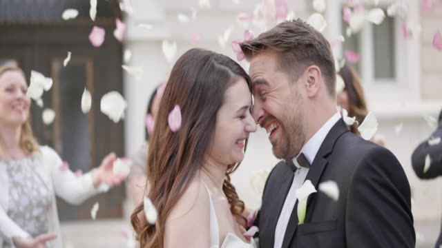 SLO MO Happy newlyweds in a rose petal shower video
