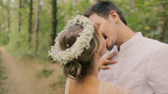 vidéos et rushes de heureux mariés debout dans le parc - composition florale