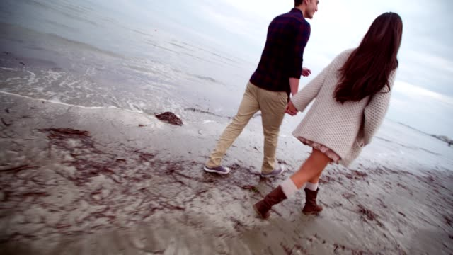 Happy newlyweds walking on the beach on their honeymoon video