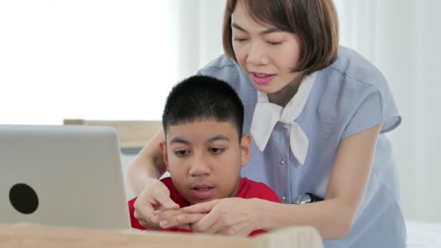 집에서 책상에 휠체어에 장애가있는 아시아 청소년 소년의 손을 잡고 아시아 여성 간병인의 행복. - giving tuesday 스톡 비디오 및 b-롤 화면