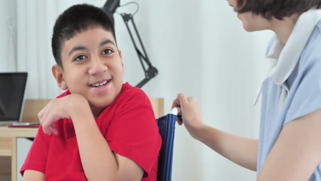 휠체어장애가 있는 아시아 청소년 소년이 집에서 아시아 의 젊은 여성 간병인과 이야기하는 것을 기쁘게 생각합니다. - giving tuesday 스톡 비디오 및 b-롤 화면