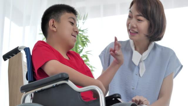 szczęśliwy z azji teenaner chłopiec z niepełnosprawnością na wózku inwalidzkim rozmowy z azji młoda opiekunka w domu. - giving tuesday filmów i materiałów b-roll