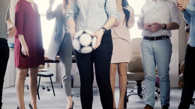 Happy office employees hold a physical activity. Young multiethnic colleagues celebrating, playing with soccer ball 4K video