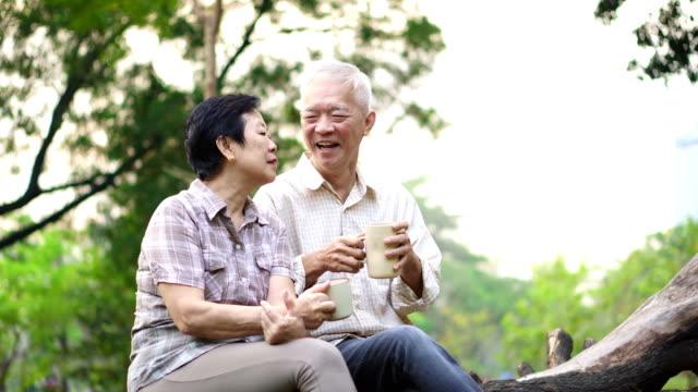 幸せな古いアジア シニア カップル朝公園でデートします。コーヒー会話 - ヘルシーなライフスタイル点の映像素材/bロール