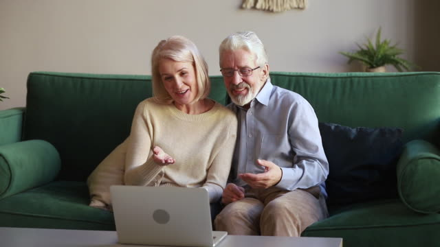 Happy old couple laughing talking making videocall looking at laptop Happy senior old couple laughing talking making distance video call looking at laptop webcam sitting on sofa, cheerful mature aged family enjoy online chat internet conversation on skype at home zoom stock videos & royalty-free footage