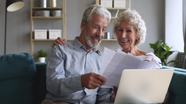Happy old couple talking checking papers holding bills and laptop Happy old couple talking checking papers holding domestic bills and laptop computer, satisfied bank clients senior grandparents customers planning budget investment loan insurance payment at home bills and taxes stock videos & royalty-free footage