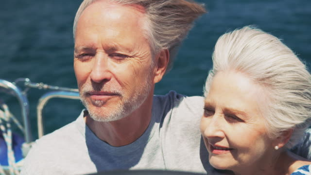 Happy old couple talking while traveling in yacht
