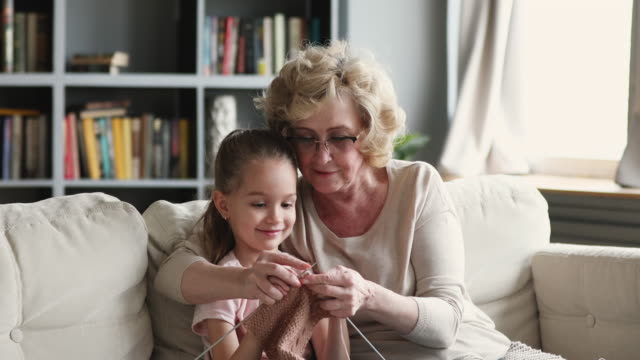Happy old granny teaching cute granddaughter learning knitting needles Happy senior old adult granny teaching small cute granddaughter learning knitting needles, two generations family grandparent and little grandchild having fun enjoying handcraft hobby concept at home granddaughter stock videos & royalty-free footage