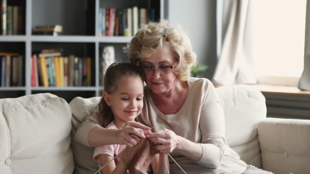 happy old granny teaching cute granddaughter learning knitting needles - nipote femmina video stock e b–roll