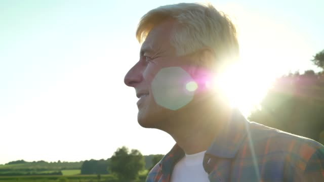 Happy old male farmer looking forward on his field and smiling, beautiful nature during sunset in background, lens flare