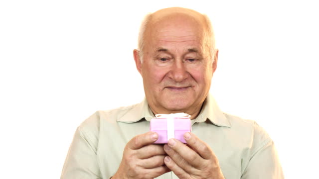 Happy old man smiling joyfully holding out a gift box to the camera video