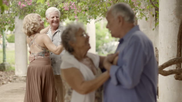 Happy old people dancing, couples of friends during dance video