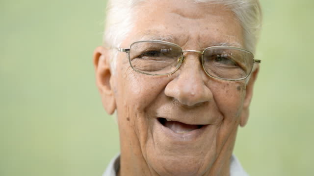 Happy old people, elderly man with eyeglasses smiling at camera video