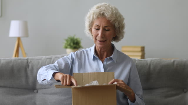 Happy old senior woman open parcel in living room Happy old senior woman customer hold open parcel box sit on sofa in living room, smiling elderly grandma customer receive post shipment online shop sale order satisfied with fast delivery concept goal post stock videos & royalty-free footage