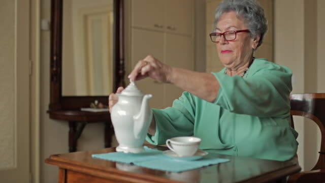 Happy old woman enjoying in afternoon tea at home and waving to the camera. video