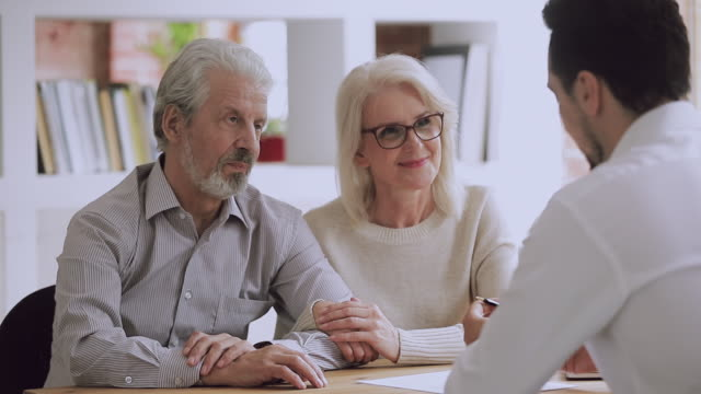 Happy older couple clients sign insurance contract handshake lawyer