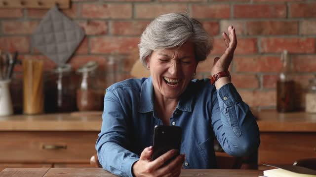 glad äldre kvinna får stora nyheter genom sms - lotteri bildbanksvideor och videomaterial från bakom kulisserna