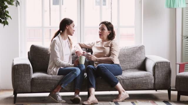 lycklig äldre mamma och vuxen dotter chattar i vardagsrummet - parent talking to child bildbanksvideor och videomaterial från bakom kulisserna