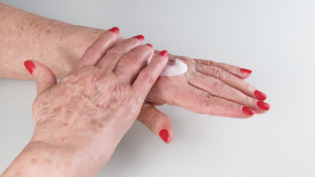 happy older woman applying hand moisturizer to keep her skin healthy happy older woman applying hand moisturizer to keep her skin healthy. Concept of hygiene, health, care lip balm stock videos & royalty-free footage