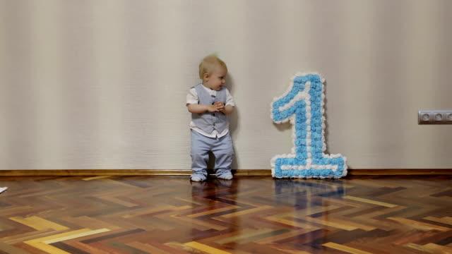 Ein fröhlicher einjähriger Junge Geburtstag feiern und tanzen auf dem Boden. – Video
