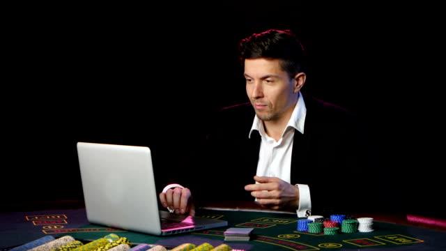 Happy online poker player winning in casino. Close up video