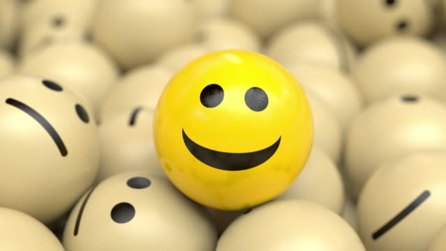 Happy optimistic ball nodding and smiling on top of a bunch of sad balls.