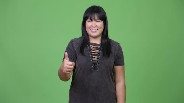 glücklich übergewichtige asiatin daumen aufgeben - einzelne frau über 30 stock-videos und b-roll-filmmaterial