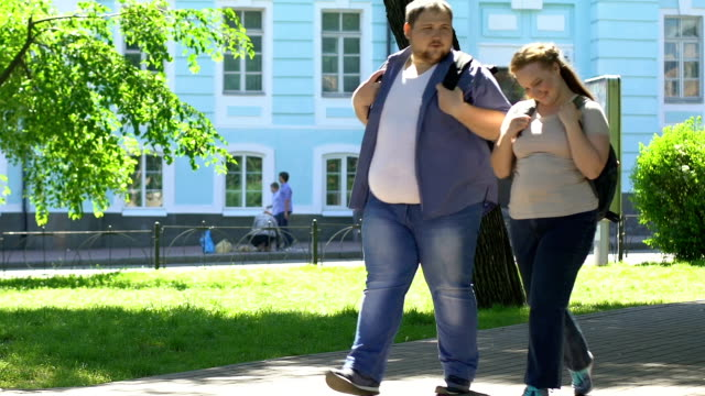 happy overweight woman and man walking in park, romantic date, body positive - sovrappeso video stock e b–roll