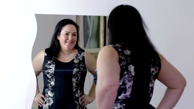 happy overweight woman looking in the mirror before going out: looking her dress video