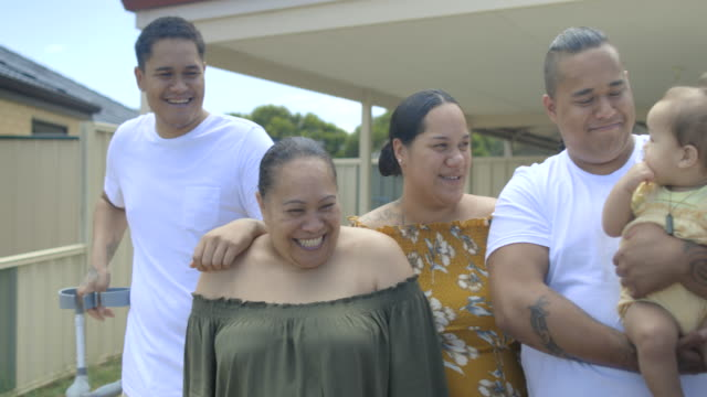 Happy Pacific Islander Family Zoom in and pan of a four generation family, standing on the driveway in front of their family home. minority groups stock videos & royalty-free footage