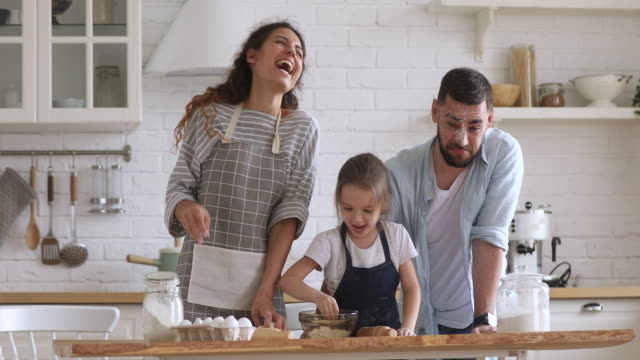 Happy parents and kid daughter kneading dough play with flour