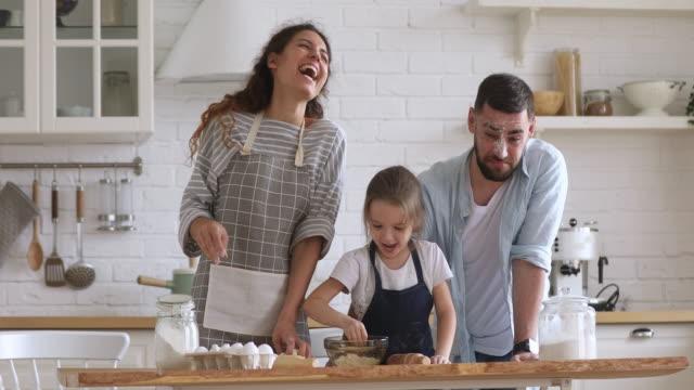 happy parents and kid daughter kneading dough play with flour - piec przygotowywać jedzenie filmów i materiałów b-roll